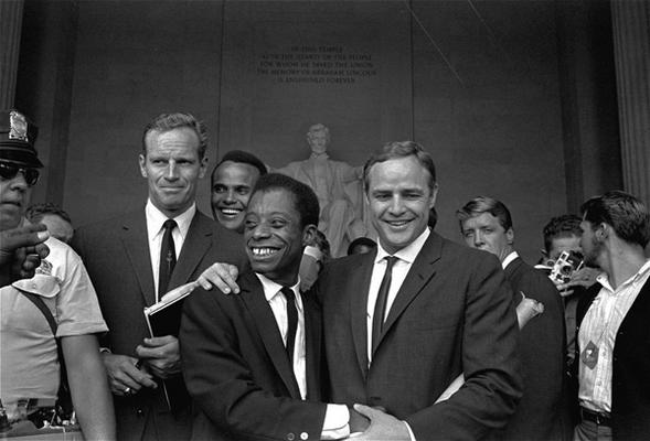 Charlton Heston and Harry Belafonte appear with Marlon Brando, who embraces James Baldwin, author and civil rights leader, in front of the Lincoln statue at the Lincoln Memorial during the March on Washington demonstration ceremonies on August 28, 1963.